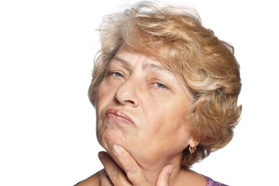 An image of the head of an older woman, thoughtfully stroking her chin.
