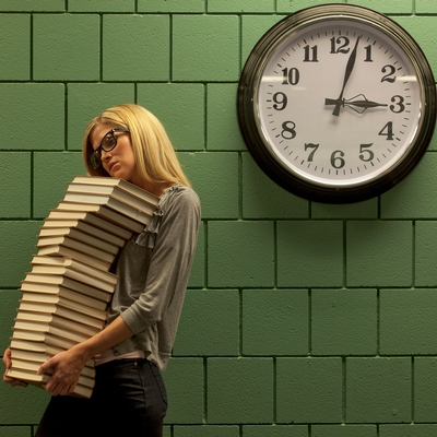 A woman is carrying a huge stack of hardcover books. She is standing in front of an institutional green brick wall on which there is a clock that says 3 o'clock.