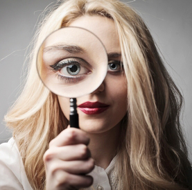 An attractive, long-haired blond woman looks straight at the camera, holding up a magnifying glass in front of her right eye, making that eye appear extremely large within the frame of the magnifying glass.