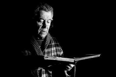 A striking black and white image of an older man with glasses perched on his nose, side lit and wearing a plaid jacket or housecoat, who is holding what looks like an old book and reading.