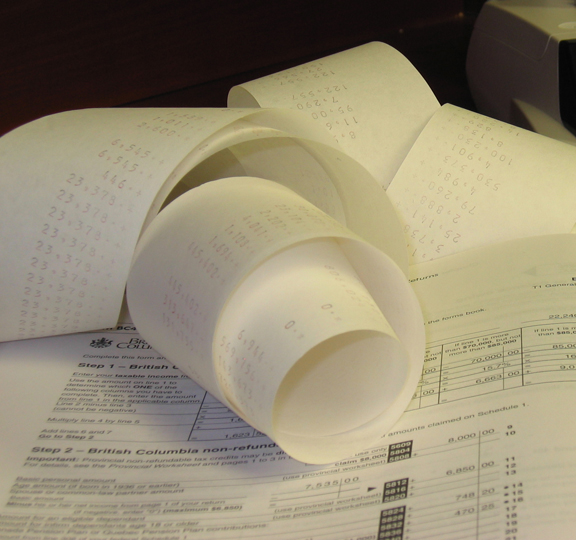 This image shows rolled-up calculations on paper from a printer calulator, set on top of a tax guide for British Columbia page.