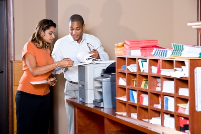 Two workers stand at a printer discussing the contents of some sheets of paper.