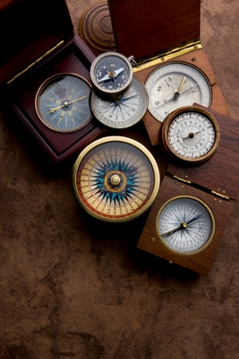 An array of antique compasses, some in wooden casings, arranged haphazardly on a dark brown surface.