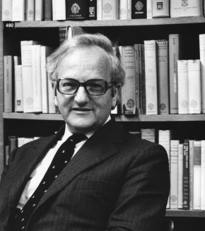 Black-and-white portrait of R. W. Burchfield, author of New Fowler's Modern English Usage, a distinguished-looking older man in a suit and tie with large, black-rimmed glasses, sitting in front of a bookshelf filled with books.