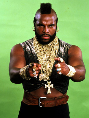 Mr T gazes and points with both hands directly at the camera. His sleeveless arms betray rippling biceps. This black, muscled icon stands silhouetted against a bright green back ground.