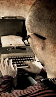 View of a man at his typewriter from over his left shoulder. The man is 30ish, has buzz-cut hair and black-rimmed glasses.