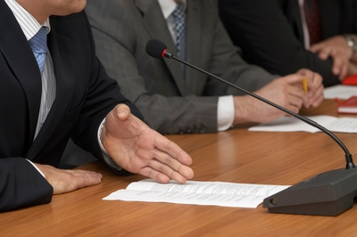 A business man sits at a desk, among other business men, talking into a mic with a sheet of paper in front of him.