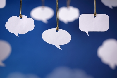 5 empty white paper thought and speech balloons, hanging from brown strings against a blue background.