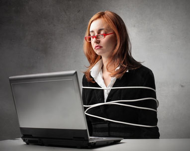 A young red-haired woman with orange-rimmed glasses sits, emotionless, in front of a computer, her torso wrapped several times with a white electrical cord.