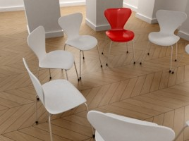 A circle of white chairs with one red chair