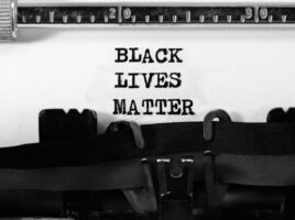 text BLACK LIVES MATTER on white background typed on a typewriter in a stark black-and-white image