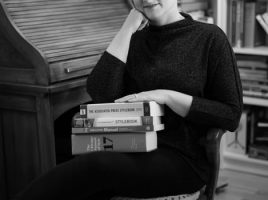 Jahleen Turnbull-Sousa poses in an office chair beside a writing desk with a stack of style guides in her lap. (© Theresa Camastra, Black Dog Studios)